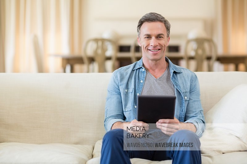Portrait of man sitting on sofa and using digital tablet in living room