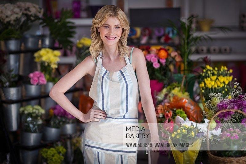Portrait of happy female florist standing in flower shop
