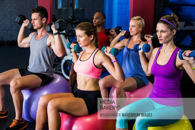 Friends holding dumbbells while exercising in gym