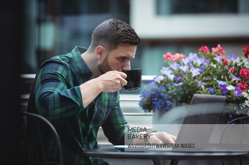 Businessman using laptop while having a cup of coffee in cafeteria