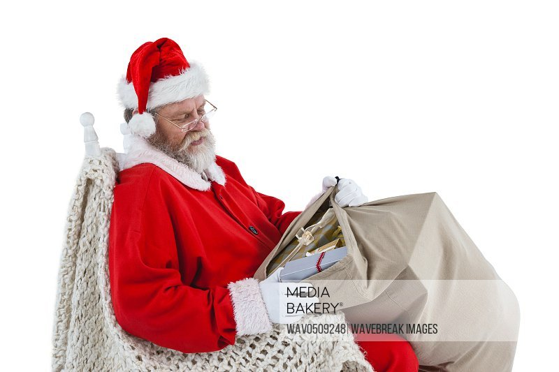 Santa claus sitting on chair and looking at gifts