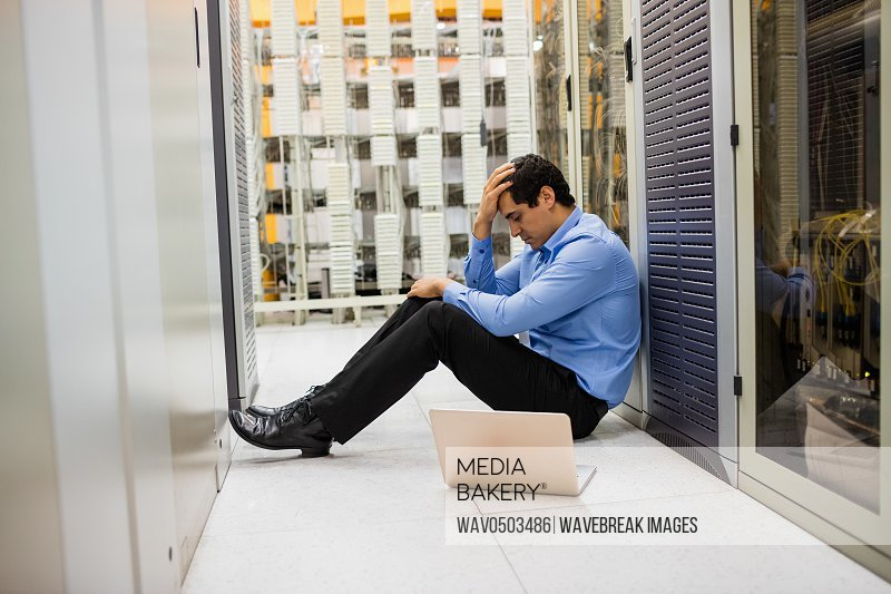 Stressed technician sitting in hallway of server room