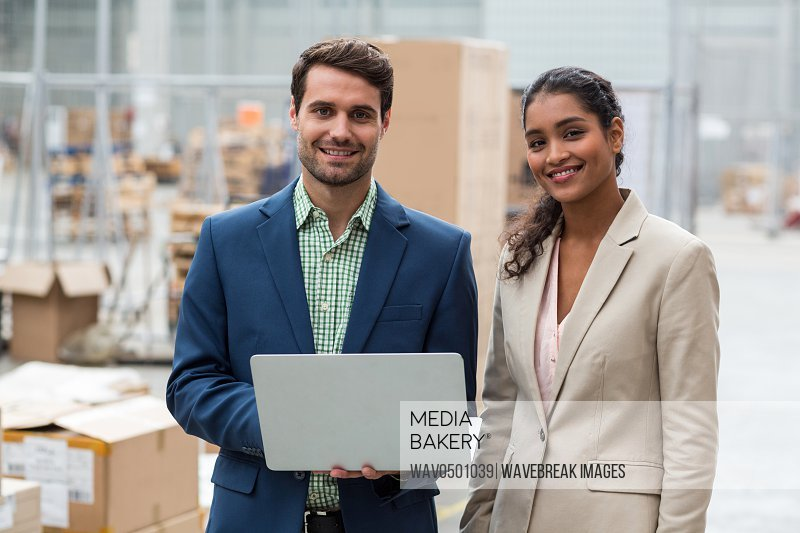 Portrait of warehouse managers standing with the laptop in warehouse