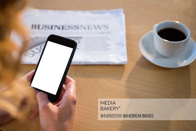 Mid section of woman using her mobile phone with newspaper and coffee cup on table