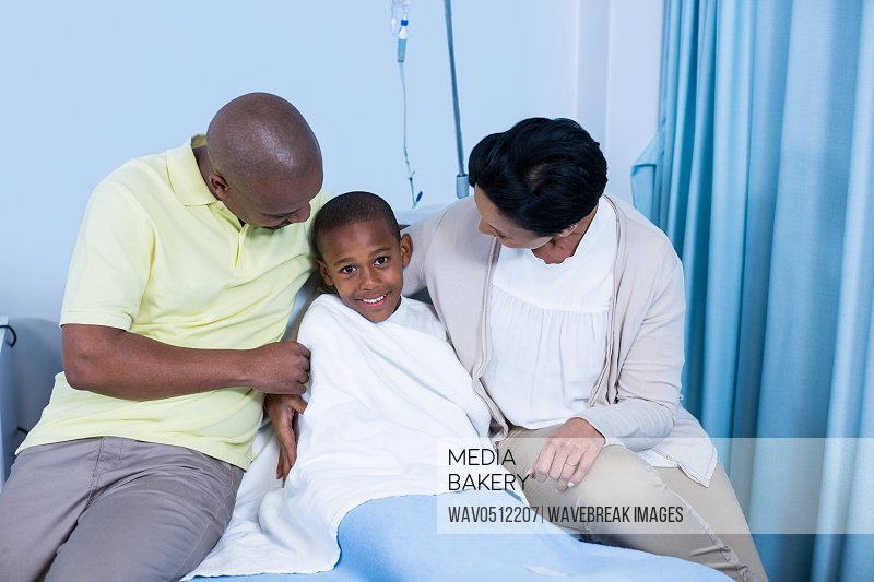 Smiling parents interacting with patient in hospital