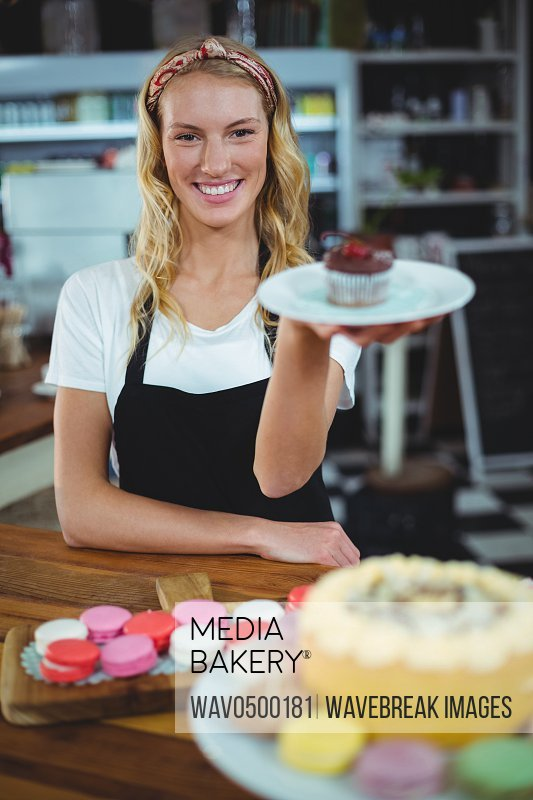 Portrait of smiling waitress holding a plate of cupcake in cafA?