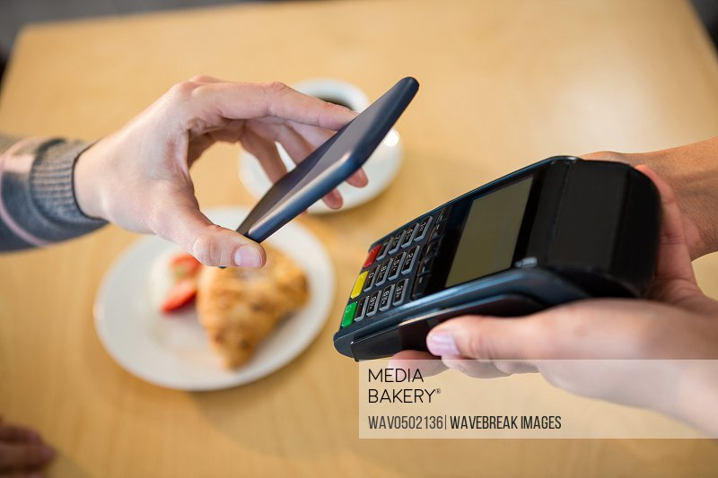 Woman making payment through smartphone in cafeteria