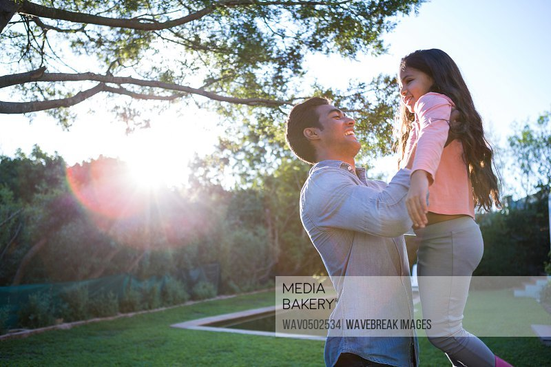 Father holding daughter in arms in the garden
