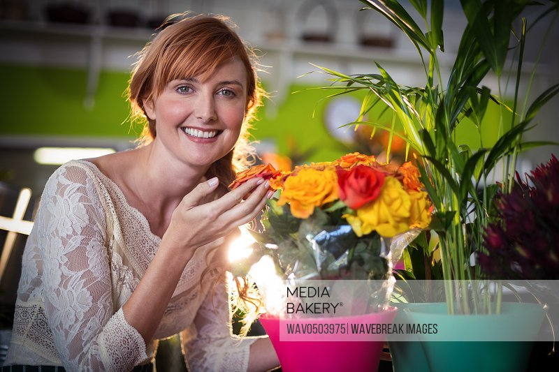 Portrait of female florist touching rose flowers in the flower shop