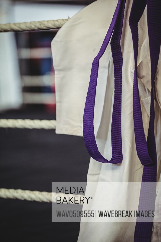 Close-up of karate uniform and purple belt in boxing ring