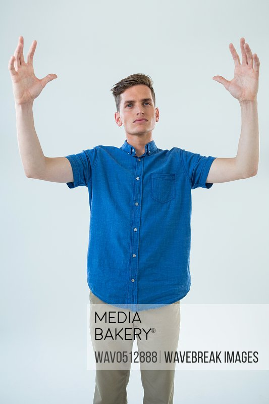 Man in blue shirt with arms raised against white background