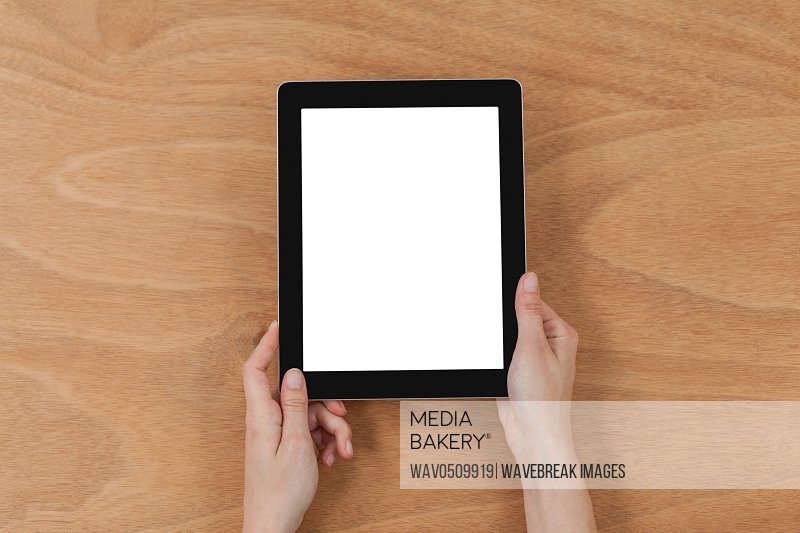 Close-up of hands holding digital tablet against wooden background
