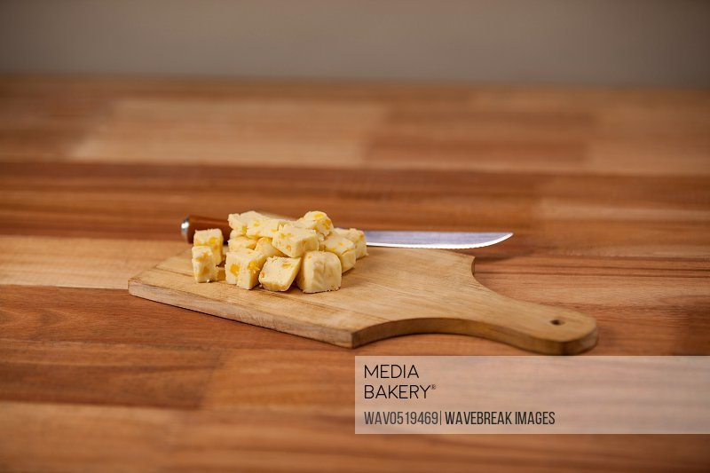 Cheese cubes and knife on wooden chopping board