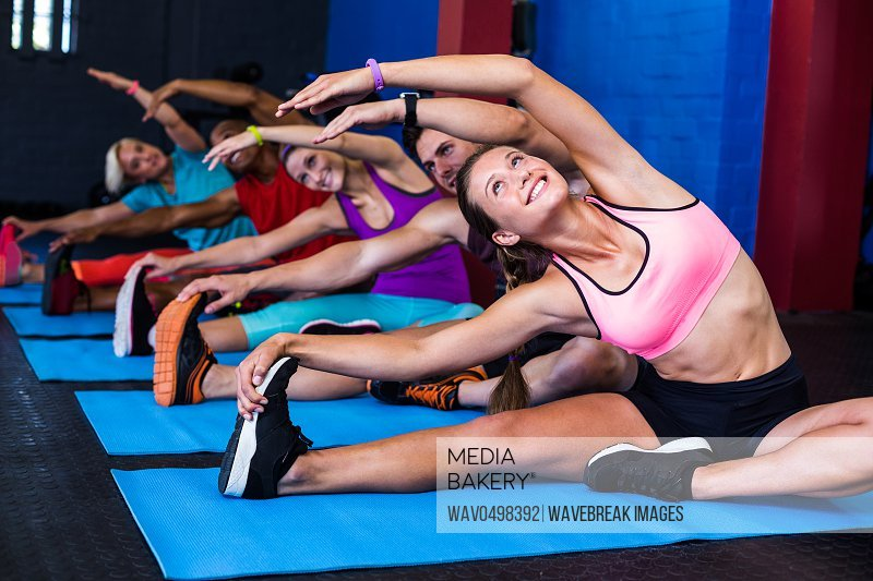Smiling people doing stretching exercise while sitting in gym