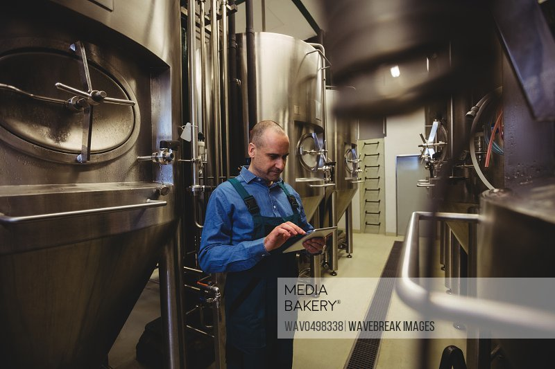 Owner using digital tablet by machinery at brewery