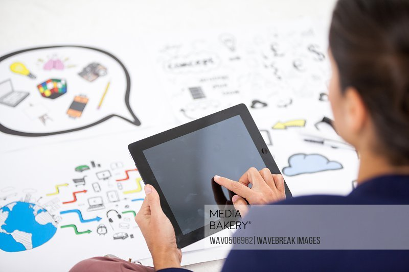 Businesswoman using digital tablet while working on icon charts