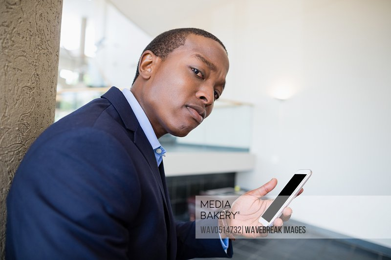 Worried businessman holding mobile phone
