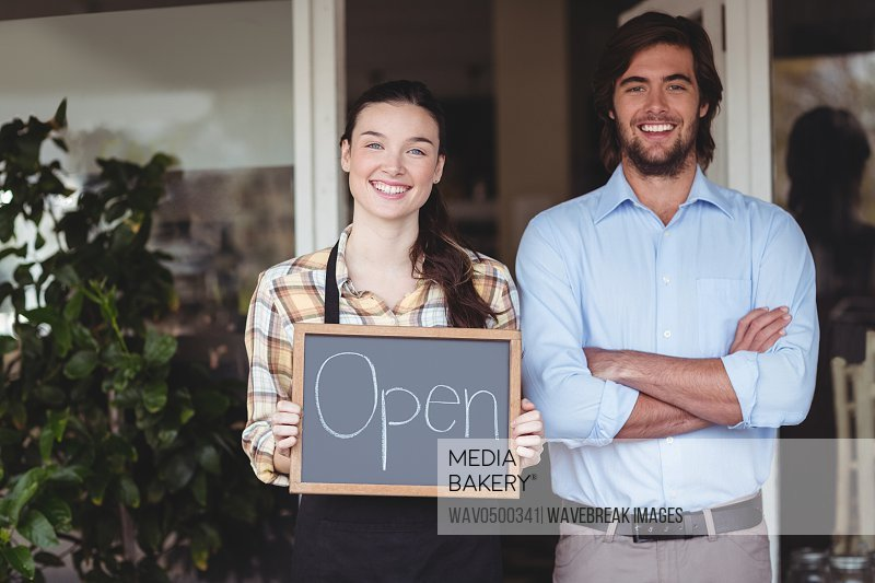 Man and waitress holding chalkboard with open sign outside the cafe