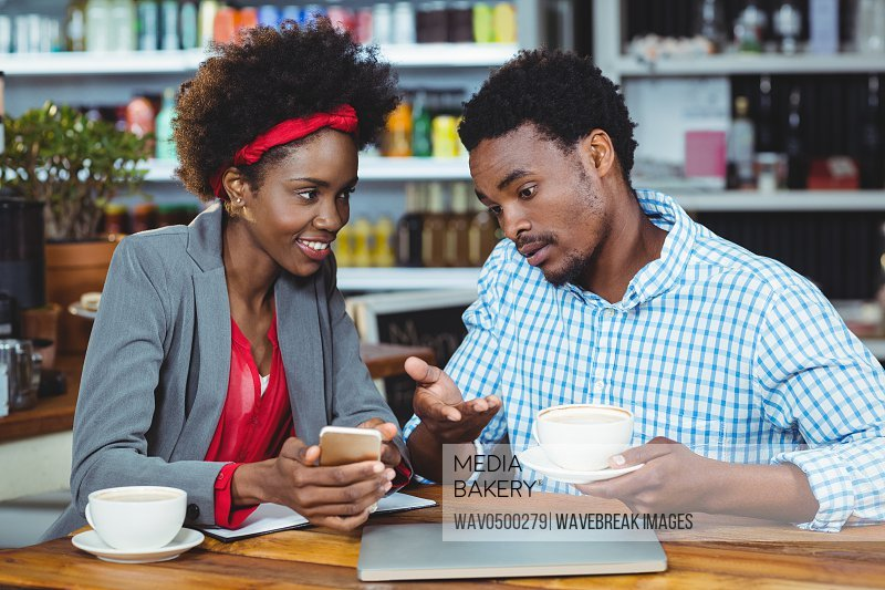 Man and woman interacting with each other while having cup of coffee in cafe