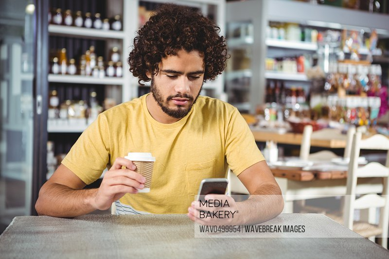 Man using mobile phone while having coffee in cafeteria