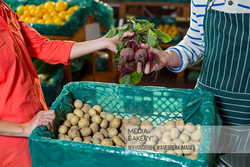 Staff assisting woman in selecting fresh beetroots in supermarket
