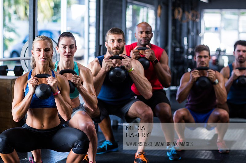 Portrait of people holding kettlebells while crouching in gym