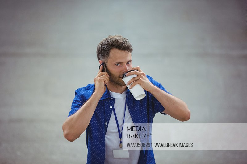 Handsome man drinking coffee while talking on mobile phone at railway platform