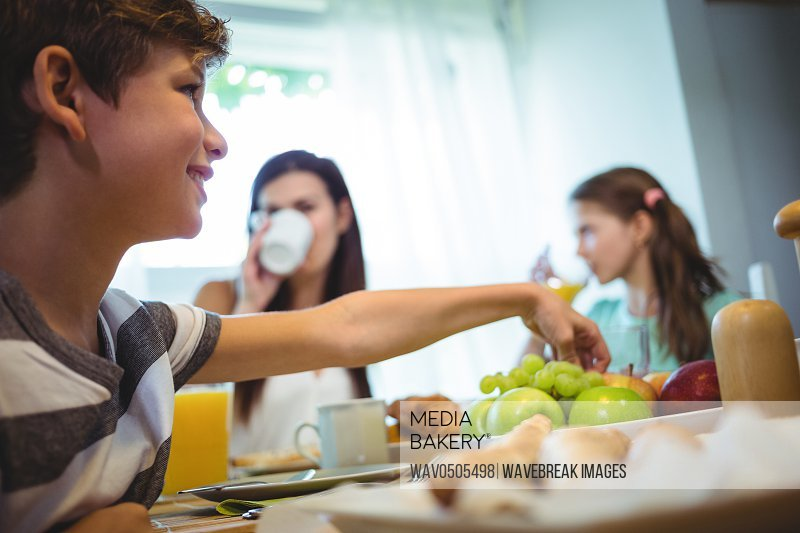 Boy picking up fruits from tray while having breakfast with family
