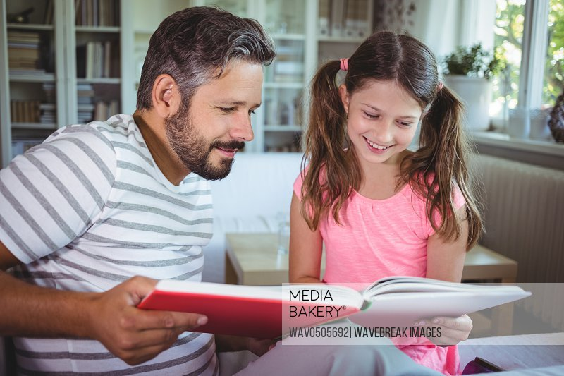 miling father and daughter looking at photo album in living room at home