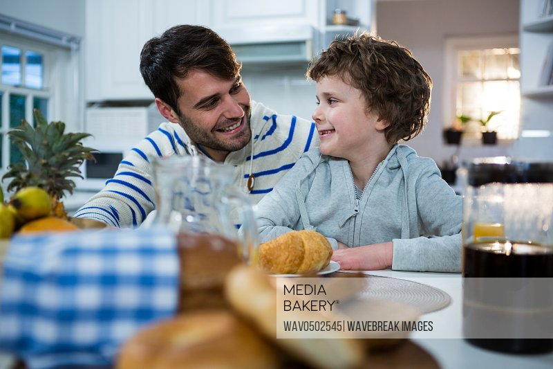 Father and son having breakfast in the kitchen at home