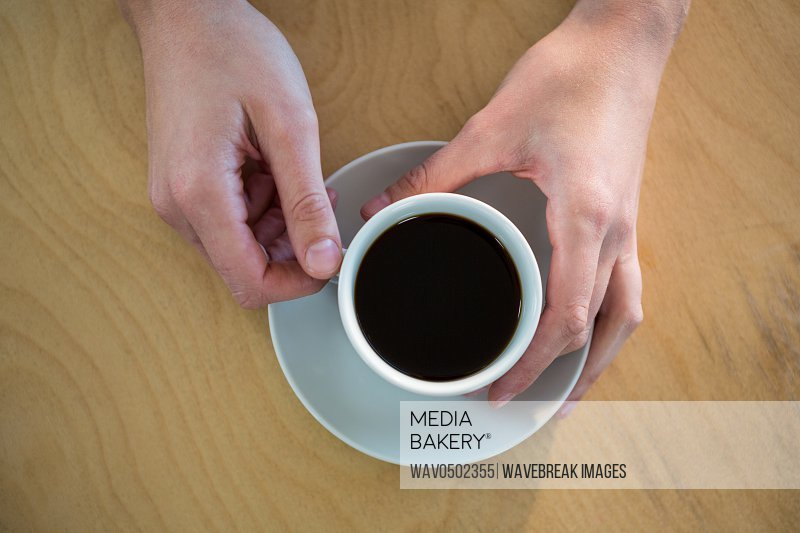 Hands holding a coffee cup in the coffee shop