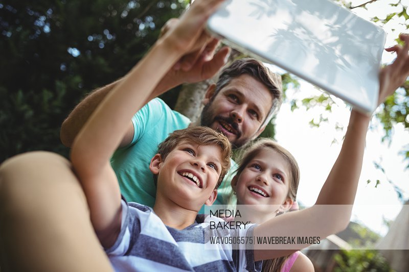 Father and kids taking a selfie in garden with digital tablet