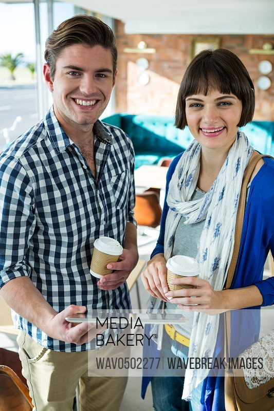 Portrait of smiling couple with coffee cups using a digital tablet in coffee shop