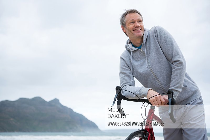 Happy man leaning on bicycle at beach