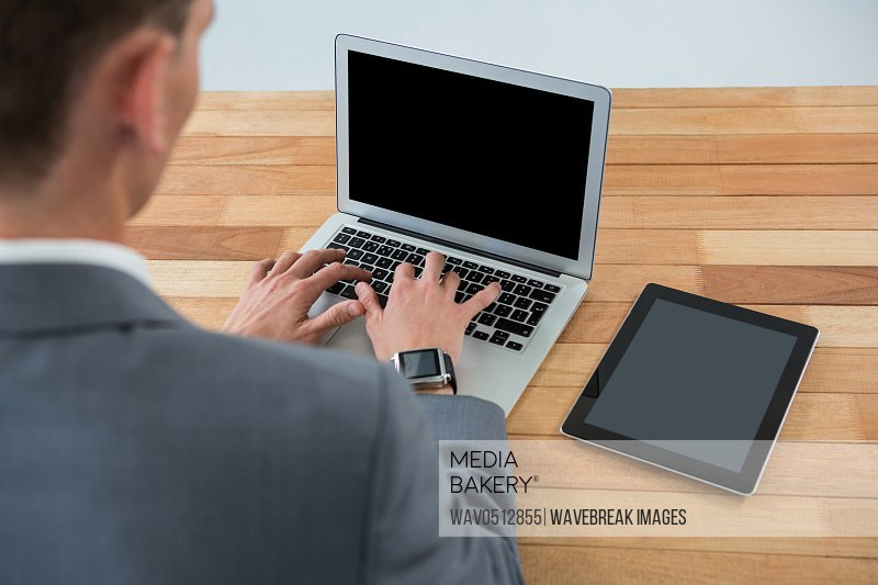 Businessman using laptop with digital tablet on table