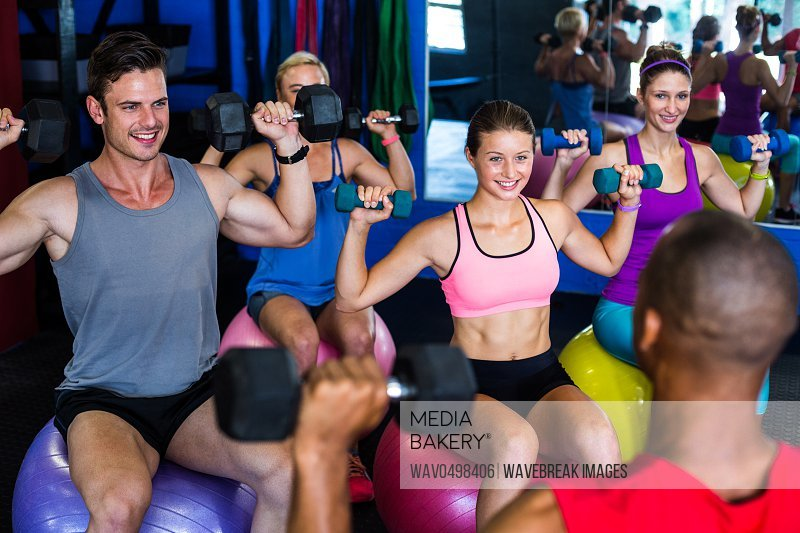 Smiling friends holding dumbbells while sitting on exercise ball in gym