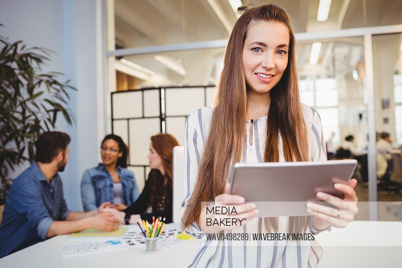 Portrait attractive businesswoman using digital tablet against coworkers in meeting room