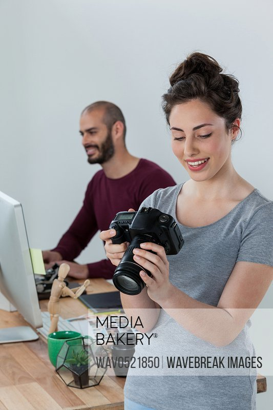 Female photographer reviewing captured photos in her digital camera