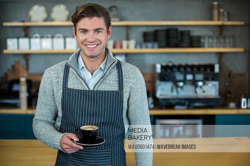 Portrait of waiter holding cup of coffee in cafA?