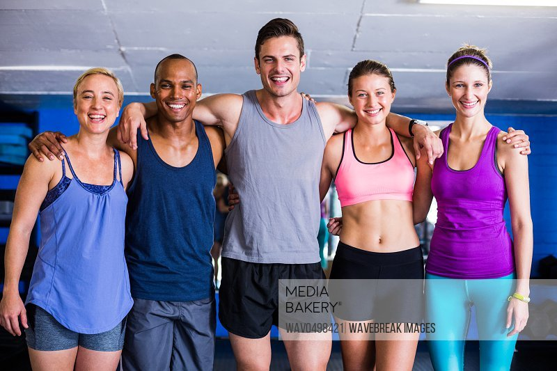 Portrait of smiling friends with arm around while standing in gym