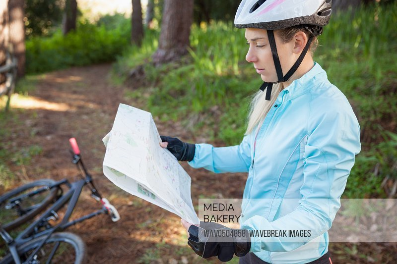 Female mountain biker looking at map in the forest