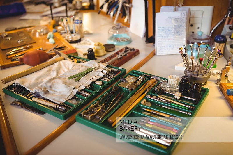 Horologist workshop with clock repairing tools, equipments and machinery in toolbox