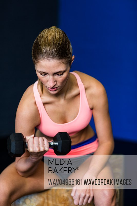 Pretty young woman exercising with dumbbell in fitness studio