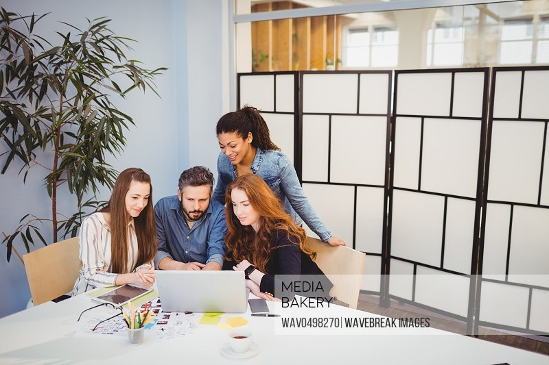 Creative business people using laptop in meeting room at office