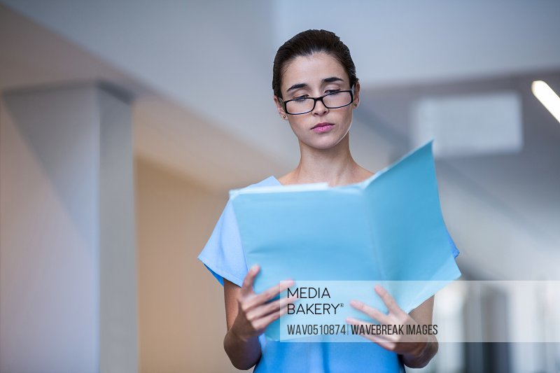 Female surgeon reading medical report at hospital
