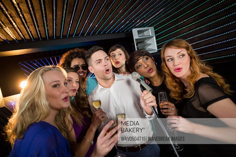 Group of happy friends singing song together while having glass of champagne in bar