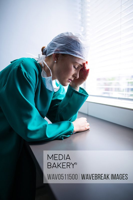 Tensed female surgeon standing at window in hospital