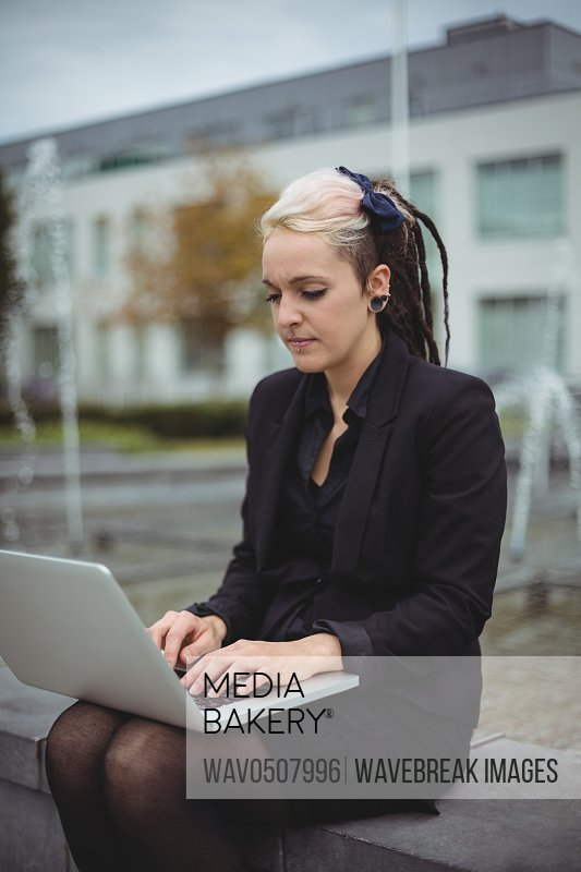 Businesswoman using laptop in office campus