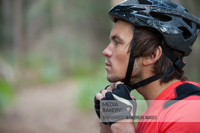 Close-up of male mountain biker wearing bicycle helmet in the forest