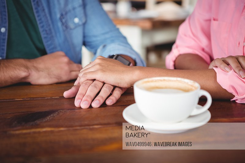 Mid-section of couple holding hands in cafeteria